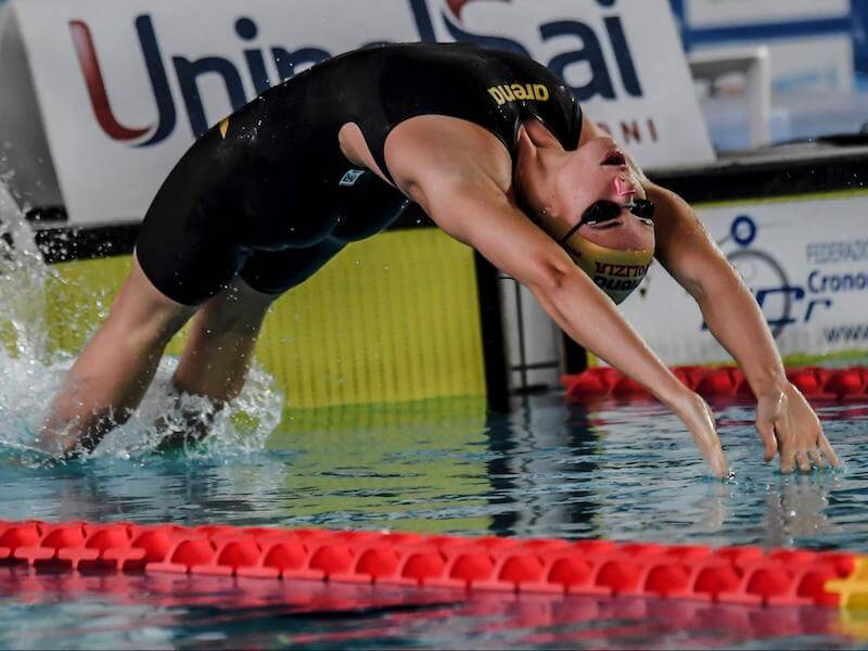 How to improve backstroke: swimmer diving into the pool into a backstroke