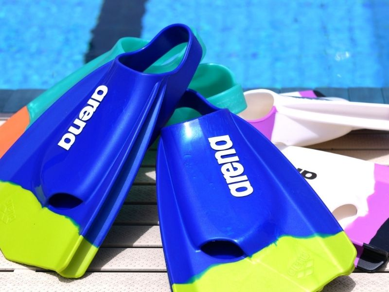 A collection of Arena swim fins poolside