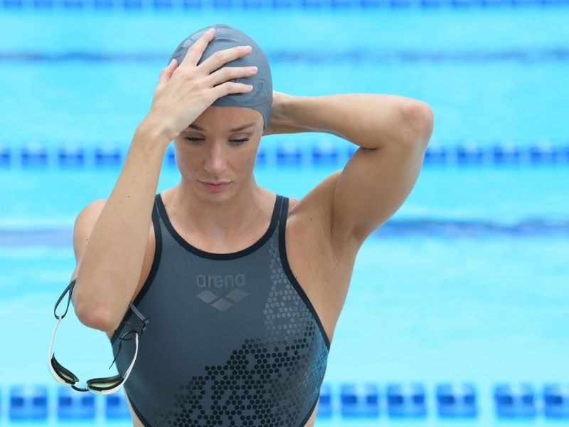 A swimmer puts on her swim cap before practice