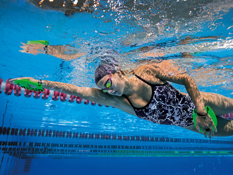 Sideview of a swimmer with swimming hand paddles