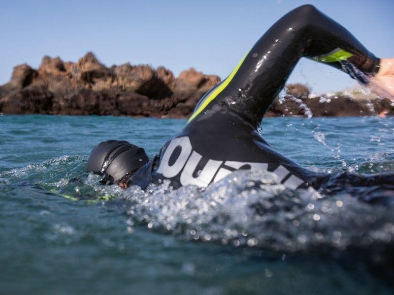 A swimmer wears Arena thermal swimwear in open water