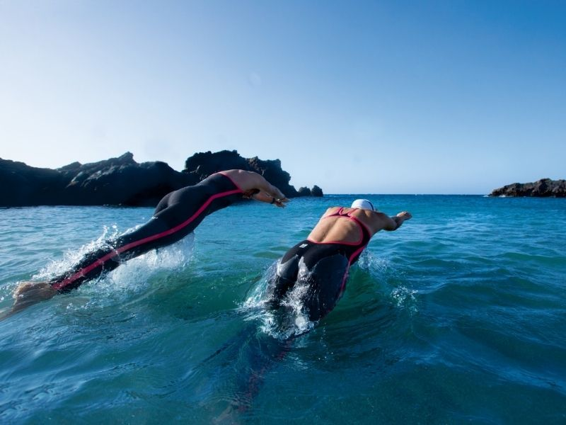 Two swimmers dive into open water