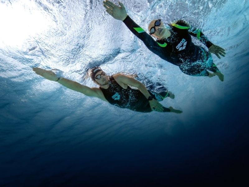 An underwater shot of two swimmers wearing Arena thermal swimwear in open water