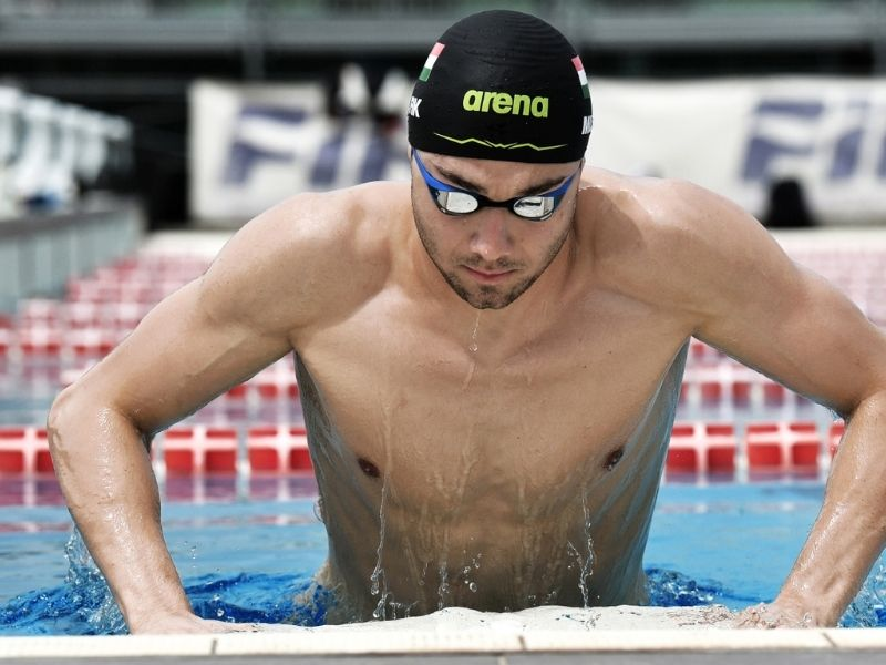 Swim training snorkel: A swimmer wearing a cap and goggles gets out of a pool