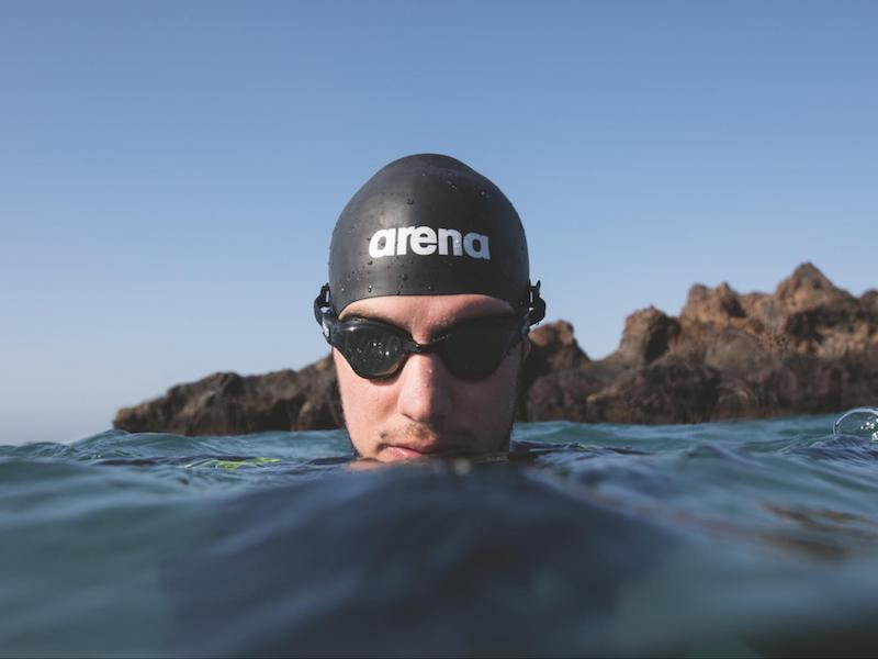 Triathlon goggles: swimmer in open water wearing googles
